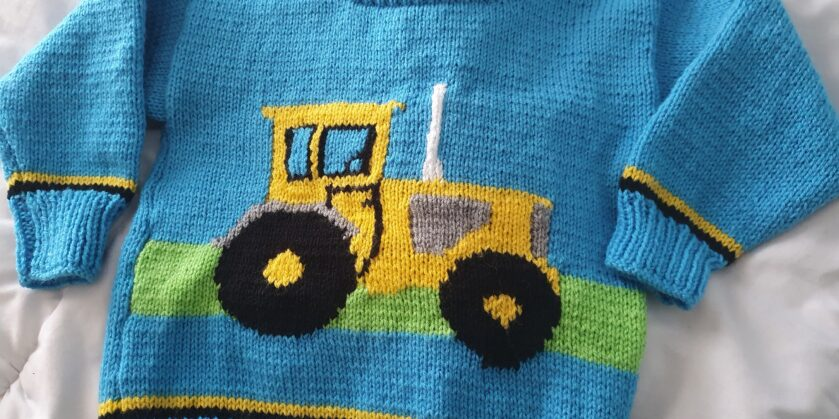 Carol's blue knitted jumper with yellow tractor on the front